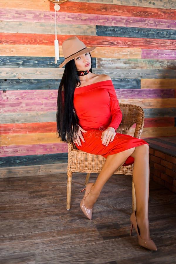 Retrato de uma mulher moreno à moda que veste um vestido vermelho, umas sapatas bege e um chapéu e sentando-se em uma cadeira fotos de stock royalty free