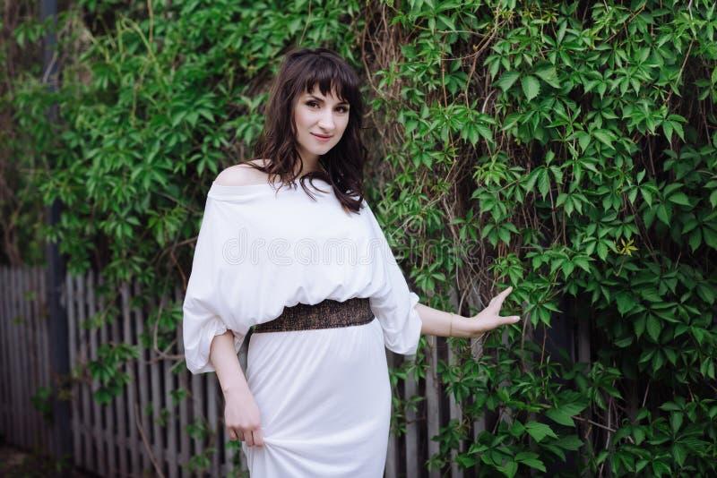 Retrato de uma mulher moreno bonita fora em um vestido branco imagem de stock