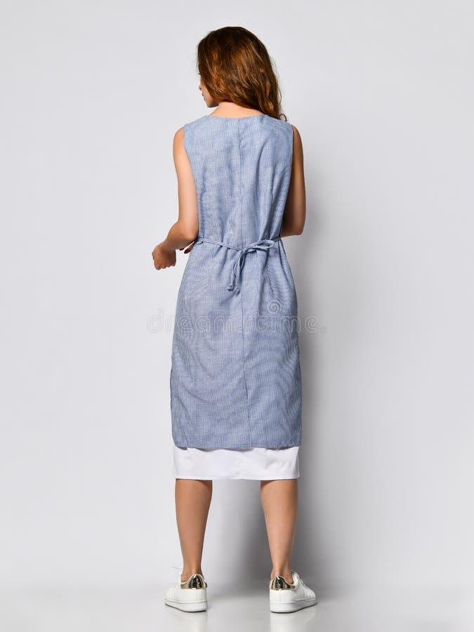 Retrato de uma mulher moreno nova em um vestido leve azul que levanta em um fundo claro, forma do ver?o, preparando-se por uma da imagem de stock