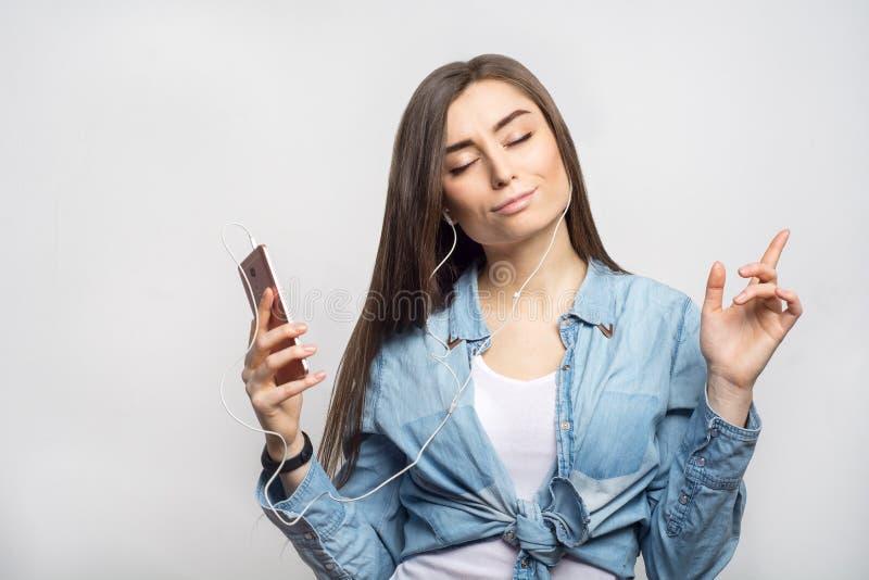 Retrato de uma mulher moreno nova que escuta a música e que dança com o smartphone em suas mãos contra o fundo branco fotos de stock