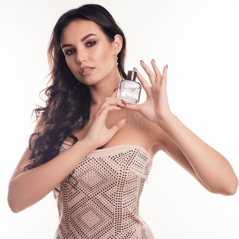 Retrato de uma mulher moreno nova sensual com uma garrafa de perfume luxuoso em suas mãos fotografia de stock