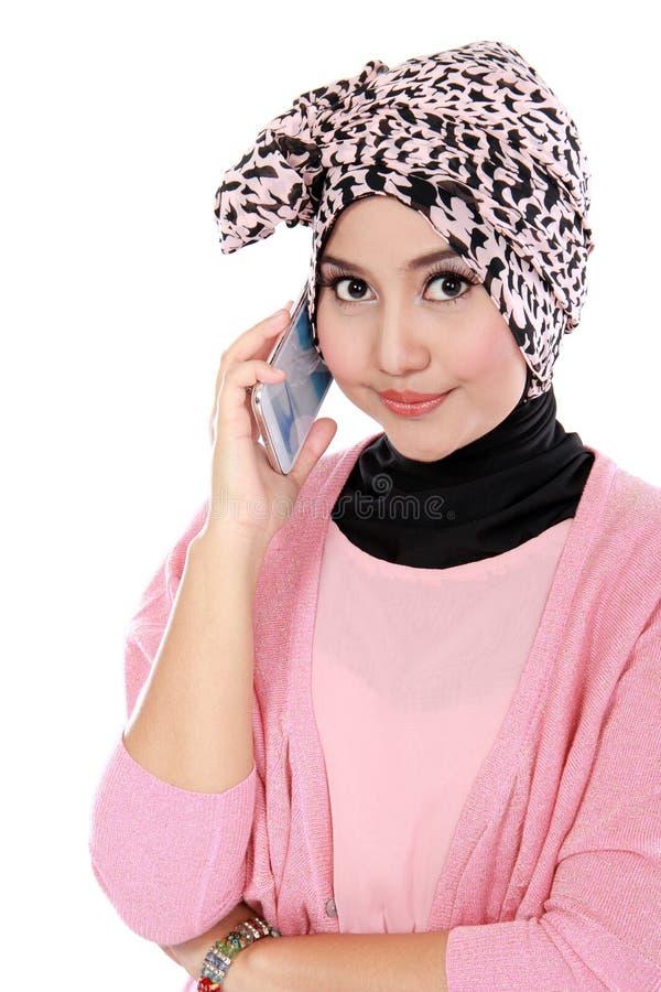 Retrato de uma mulher muçulmana asiática que fala no telefone celular imagens de stock
