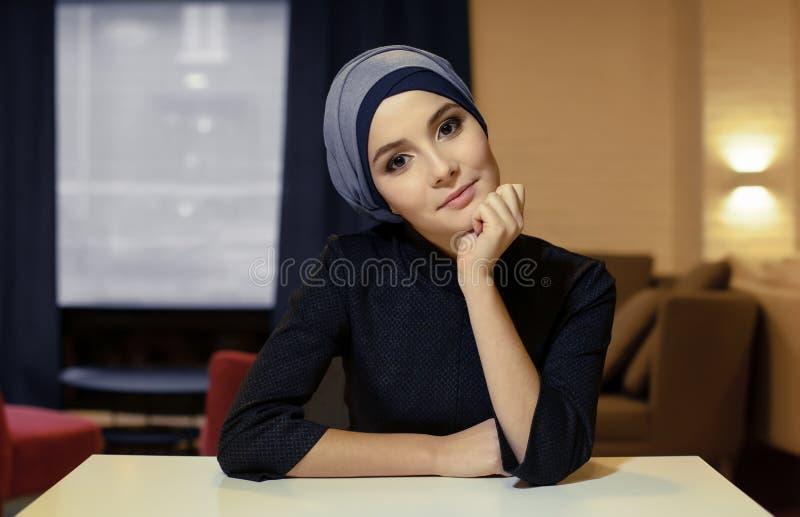 Retrato de uma mulher muçulmana nova bonita que senta-se em uma tabela imagem de stock