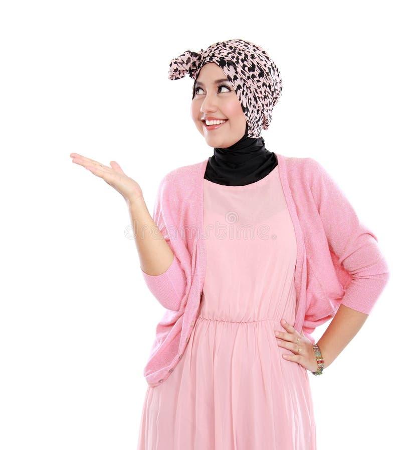 Retrato de uma mulher muçulmana nova que mostra a área vazia imagens de stock
