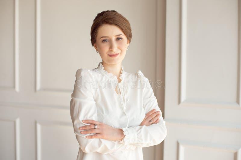 Retrato de uma mulher de negócio bonita nova em uma camisa branca e em umas calças pretas com um penteado uma polia da morena den imagem de stock