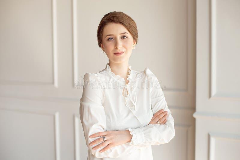 Retrato de uma mulher de negócio bonita nova em uma camisa branca e em umas calças pretas com um penteado uma polia da morena den fotografia de stock royalty free