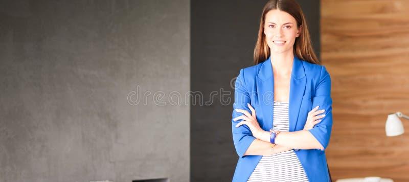 Retrato de uma mulher de negócio bonita que está perto de seu local de trabalho imagem de stock