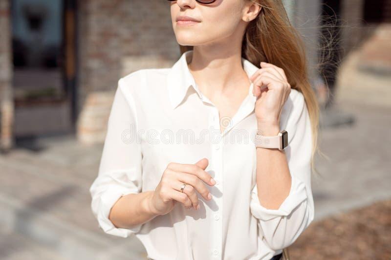 Retrato de uma mulher de negócio feliz bem sucedida em uma camisa branca e em óculos de sol O relógio esperto em uma mão está no fotografia de stock