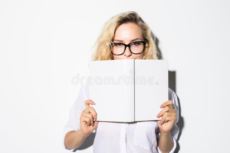 Retrato de uma mulher de negócio nova que esconde atrás de um livro com vidros, isolado em um fundo cinzento foto de stock royalty free
