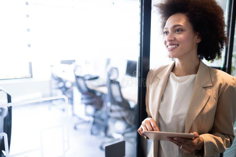 Retrato de uma mulher de negócios africana nova atrativa que sorri ao estar por janelas no escritório fotos de stock royalty free