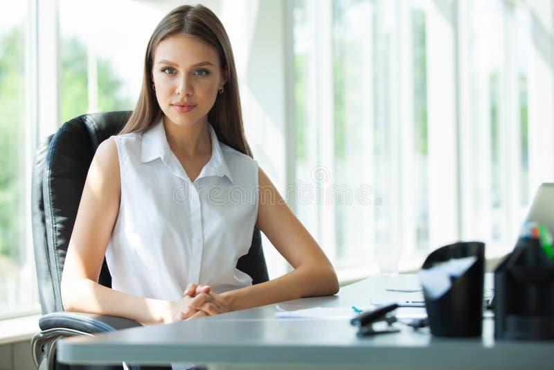 Retrato de uma mulher de negócios alegre que senta-se na tabela no escritório e que olha a câmera imagem de stock royalty free