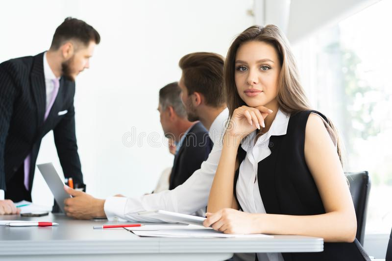Retrato de uma mulher de negócios alegre que senta-se na tabela no escritório e que olha a câmera imagem de stock