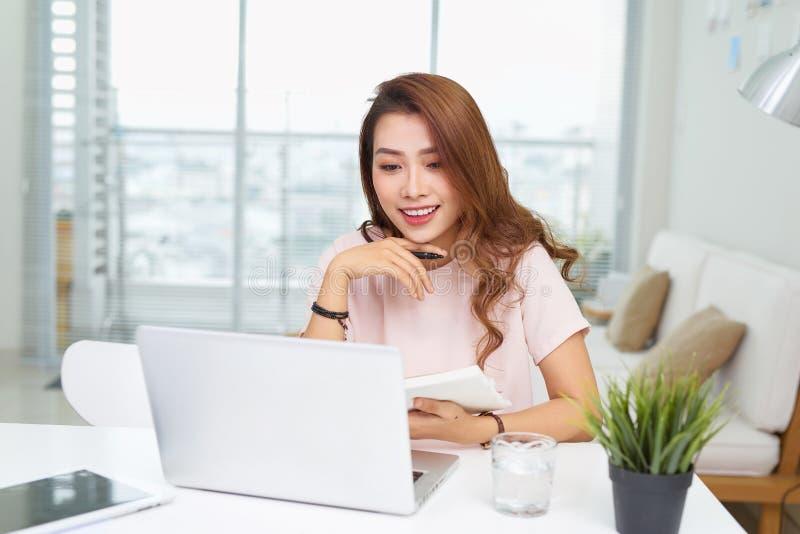 Retrato de uma mulher de negócios alegre que senta-se na tabela no escritório e que olha a câmera imagens de stock