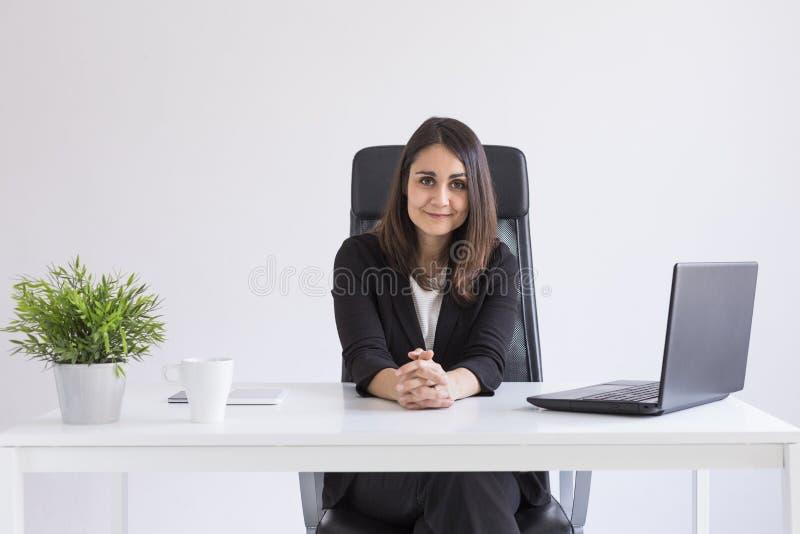Retrato de uma mulher de negócios bonita nova que trabalha no escritório e que olha a câmera Conceito do negócio Fundo branco fotografia de stock royalty free