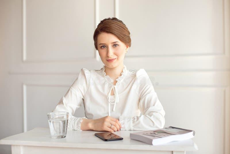 Retrato de uma mulher de negócios moreno nova de sorriso bonita em uma camisa branca que senta-se em uma estação de trabalho mode fotos de stock