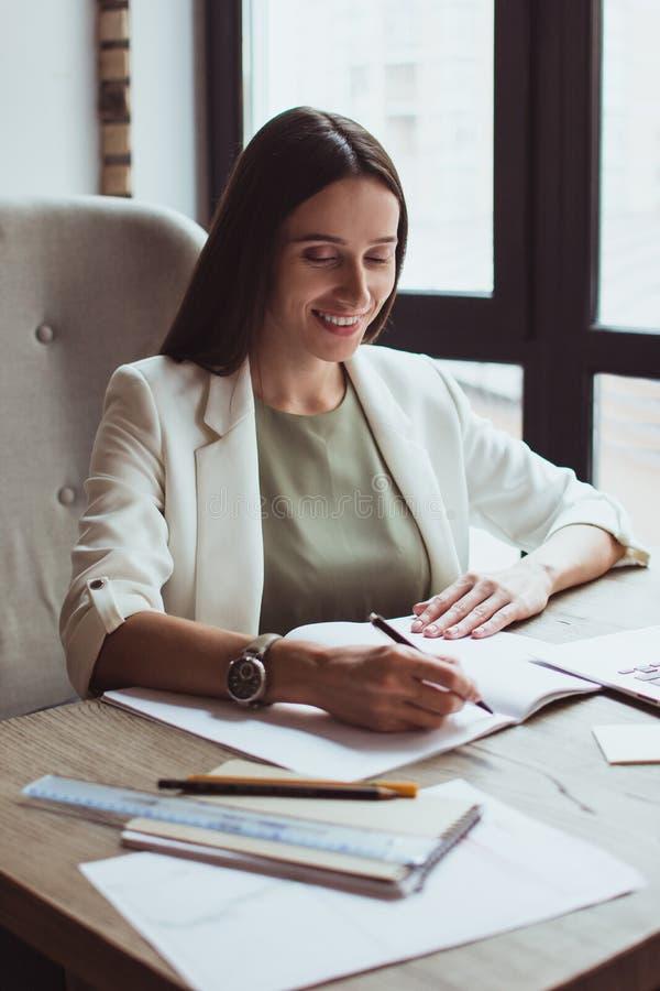 Retrato de uma mulher de negócios nova que senta-se com seu portátil no escritório fotografia de stock