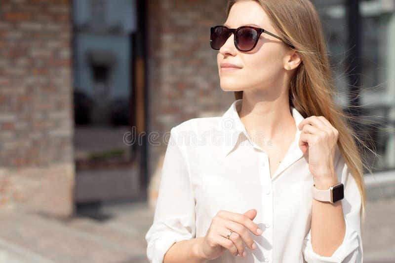 Retrato de uma mulher de neg?cio feliz bem sucedida em uma camisa branca e em ?culos de sol O rel?gio esperto em uma m?o est? no foto de stock royalty free