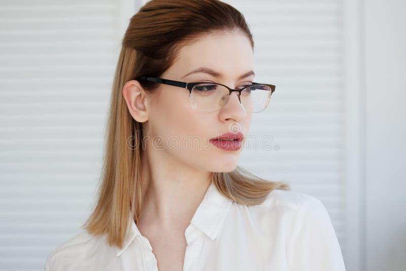 Retrato de uma mulher de neg?cio ? moda nova em uma camisa branca e em vidros imagens de stock royalty free