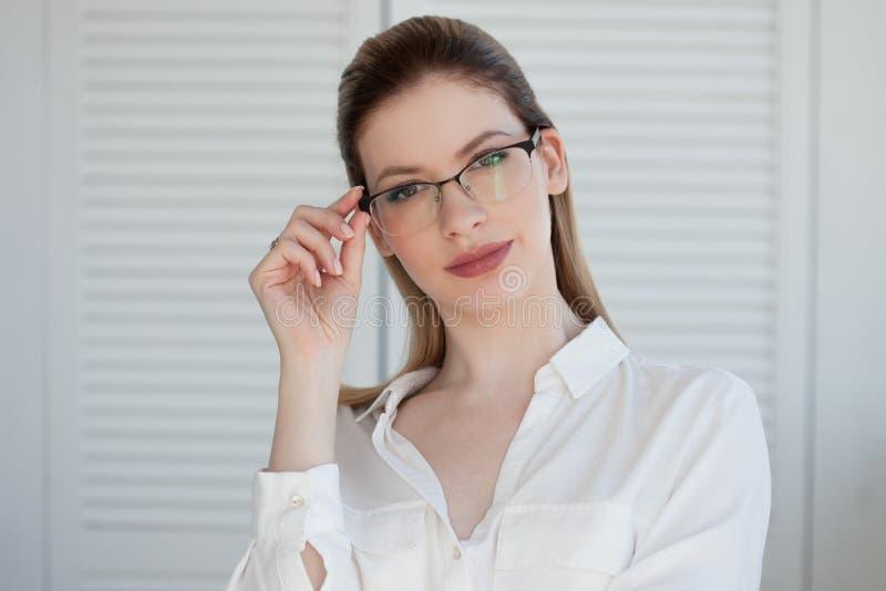 Retrato de uma mulher de neg?cio ? moda nova em uma camisa branca e em vidros fotos de stock royalty free