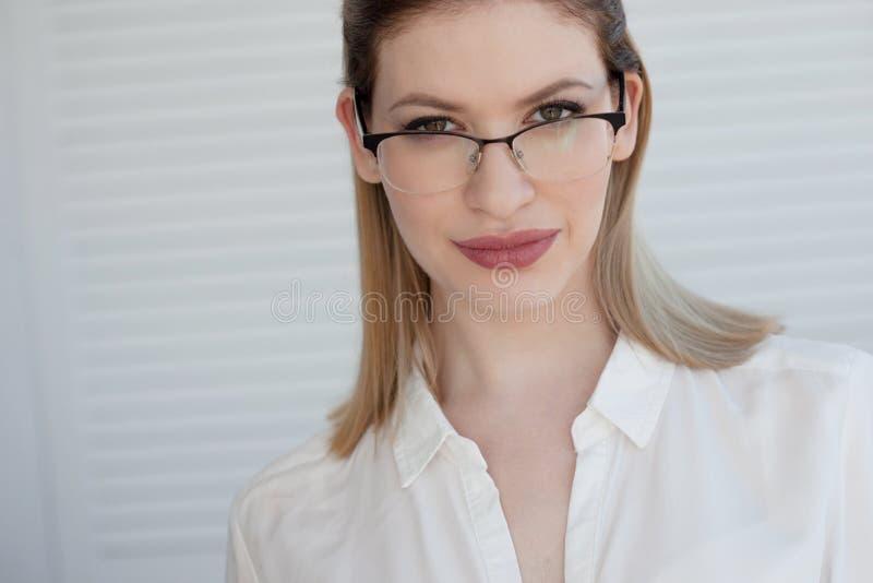 Retrato de uma mulher de neg?cio ? moda nova em uma camisa branca e em vidros foto de stock royalty free