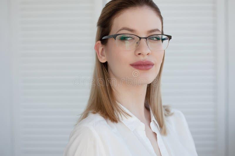 Retrato de uma mulher de neg?cio ? moda nova em uma camisa branca e em vidros imagens de stock