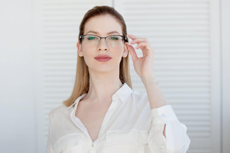 Retrato de uma mulher de neg?cio ? moda nova em uma camisa branca e em vidros fotografia de stock
