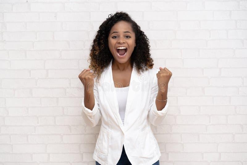 Retrato de uma mulher negra afro-americana de sorriso na roupa ocasional que aumenta seus punhos com a cara deleitada de sorriso  fotografia de stock