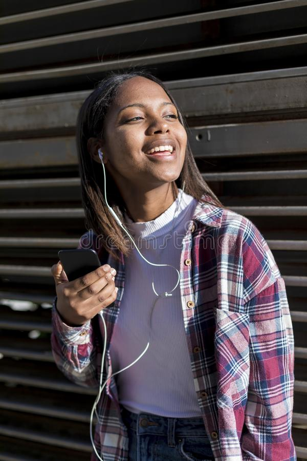 Retrato de uma mulher negra nova que escuta a música com fones de ouvido ao inclinar-se em uma cerca metálica imagens de stock royalty free
