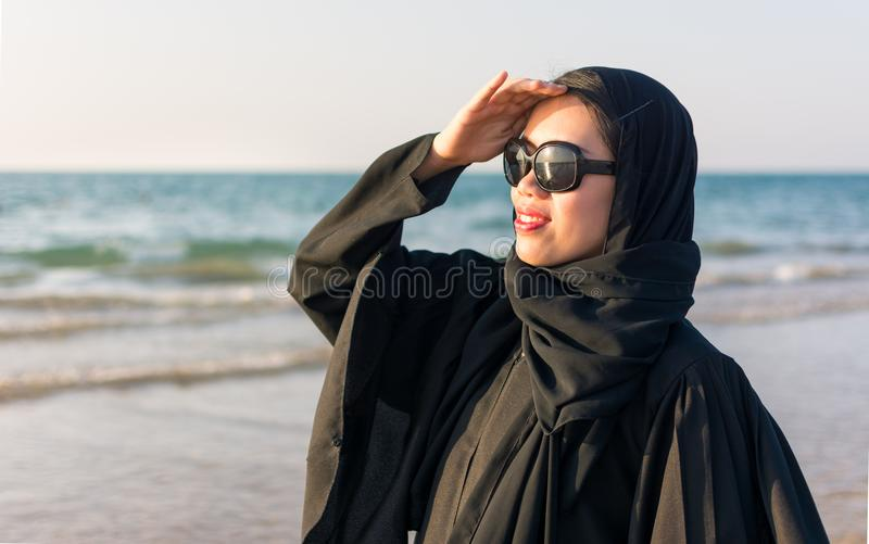 Retrato de uma mulher no abaya na praia imagens de stock