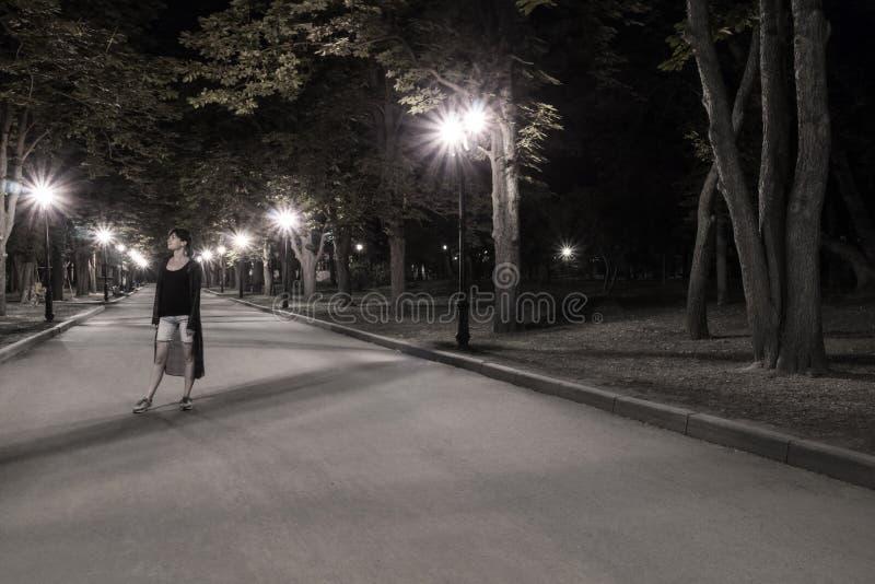 Retrato de uma mulher no parque da noite imagem de stock
