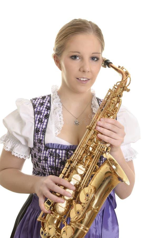 Retrato de uma mulher no vestido do dirndl com saxofone foto de stock royalty free