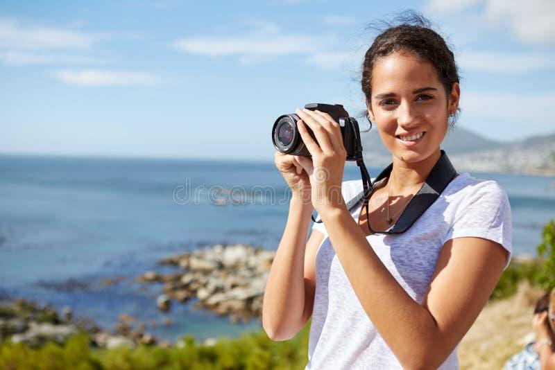 Retrato de uma mulher nova, atrativa que está perto dos wi do oceano fotografia de stock