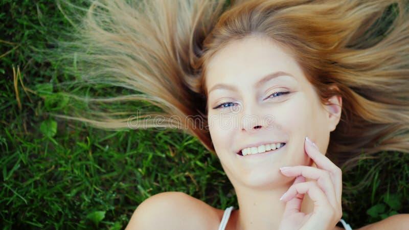 Retrato de uma mulher nova com cabelo longo Encontra-se no gramado, suas mentiras do cabelo belamente na grama imagem de stock
