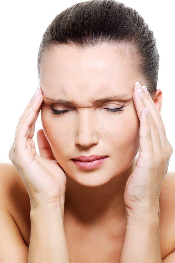 Retrato de uma mulher nova com dor de cabeça forte fotografia de stock royalty free