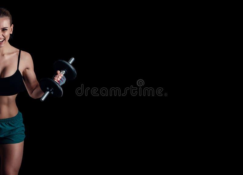Retrato de uma mulher nova da aptidão no sportswear que faz o exercício com pesos no fundo preto Menina atlética 'sexy' bronzeada imagem de stock