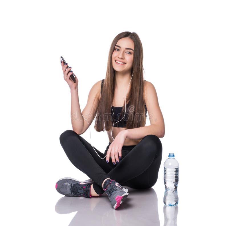 Retrato de uma mulher nova do atleta que escuta a música com os fones de ouvido sobre o fundo branco Conversa atrativa da menina  fotografia de stock royalty free