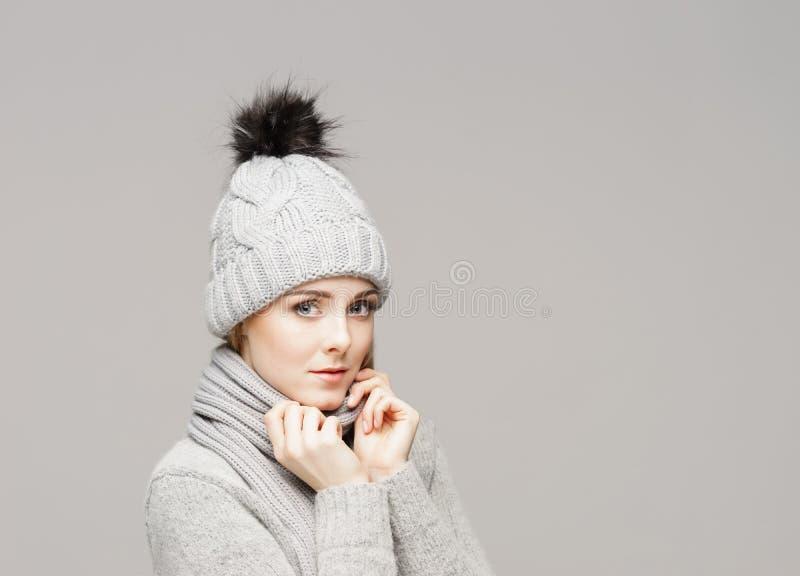 Retrato de uma mulher nova e bonita em um chapéu do inverno sobre o fundo cinzento imagens de stock