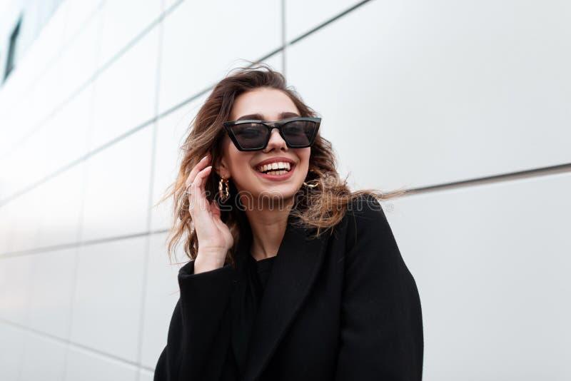 Retrato de uma mulher nova europeia alegre do moderno em óculos de sol escuros na moda à moda no revestimento elegante no sorriso fotos de stock royalty free