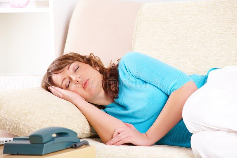 Retrato de uma mulher nova que dorme no sofá imagens de stock