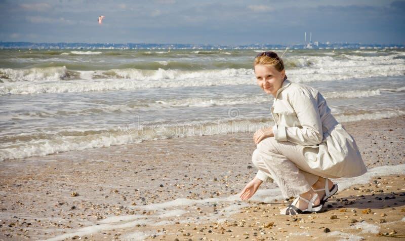 Retrato de uma mulher pensativa nova na costa perto da ressaca do oceano imagem de stock royalty free