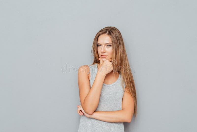 Retrato de uma mulher pensativa nova que olha a câmera fotografia de stock royalty free