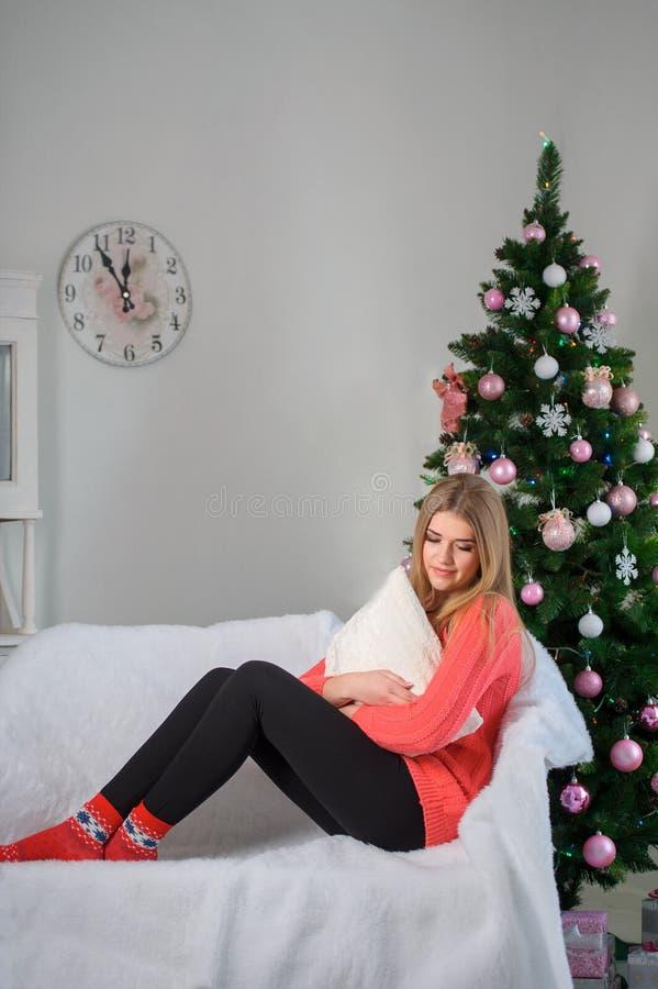 Retrato de uma mulher perto de uma árvore de Natal Menina em um vermelho de lã foto de stock royalty free