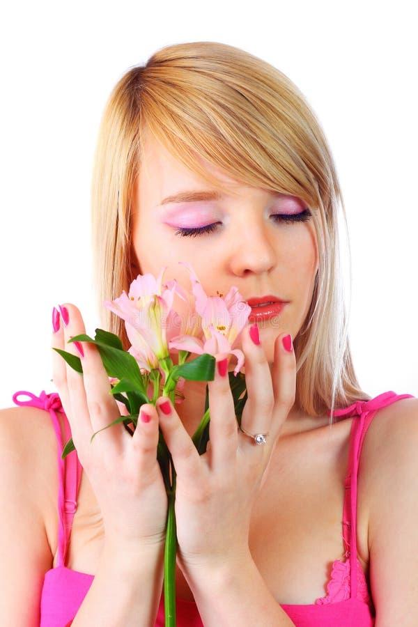 Retrato de uma mulher que prende flores cor-de-rosa imagem de stock