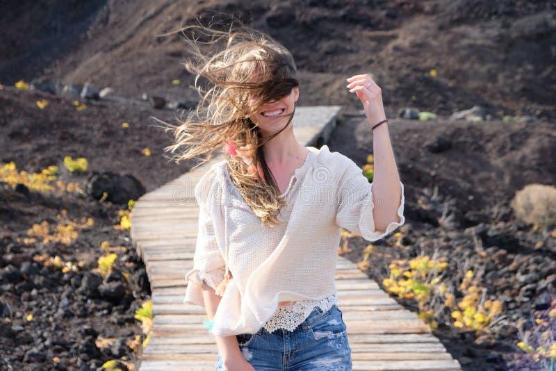 Retrato de uma mulher que sorri com cabelo louro longo por todo o lado em seu faceGirl que anda no trajeto de madeira ventoso com foto de stock