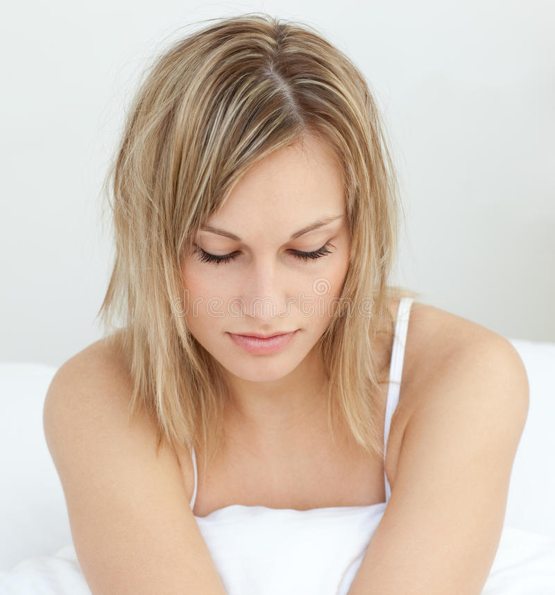 Retrato de uma mulher radiante que senta-se em sua cama fotografia de stock