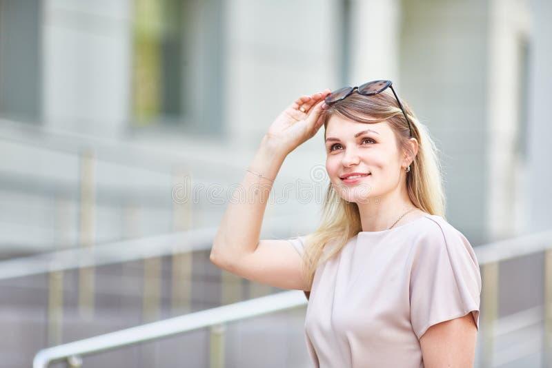 Retrato de uma mulher romântica com óculos de sol que sorria sinceramente em um dia ensolarado na mola fotografia de stock