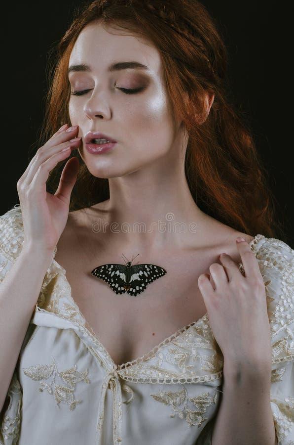 Retrato de uma mulher ruivo nova em um vestido da cinza do vintage com aberto para trás e de ombros em um fundo preto Uma borbole foto de stock royalty free