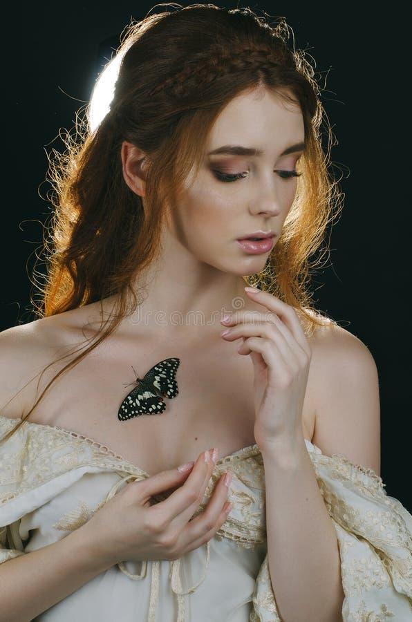 Retrato de uma mulher ruivo nova em um vestido da cinza do vintage com aberto para trás e de ombros em um fundo preto Uma borbole fotografia de stock