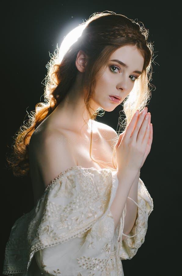 Retrato de uma mulher ruivo nova rezando no vestido da cinza do vintage com ombros abertos em um fundo preto no luminoso Um prínc imagens de stock