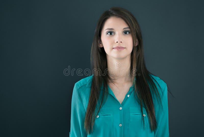 Retrato de uma mulher séria nova isolada em uma placa preta imagem de stock